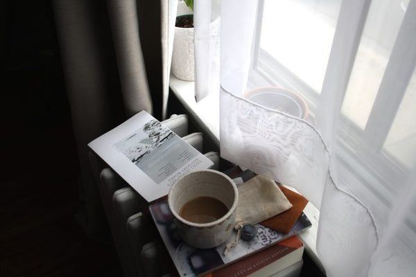 cup of coffee on a windowsill with books