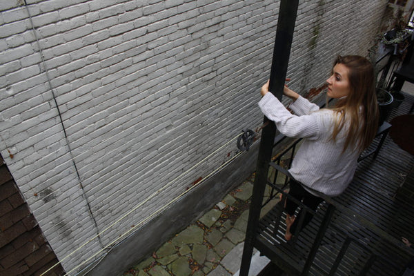 me sitting on a fire escape in an ivory sweater