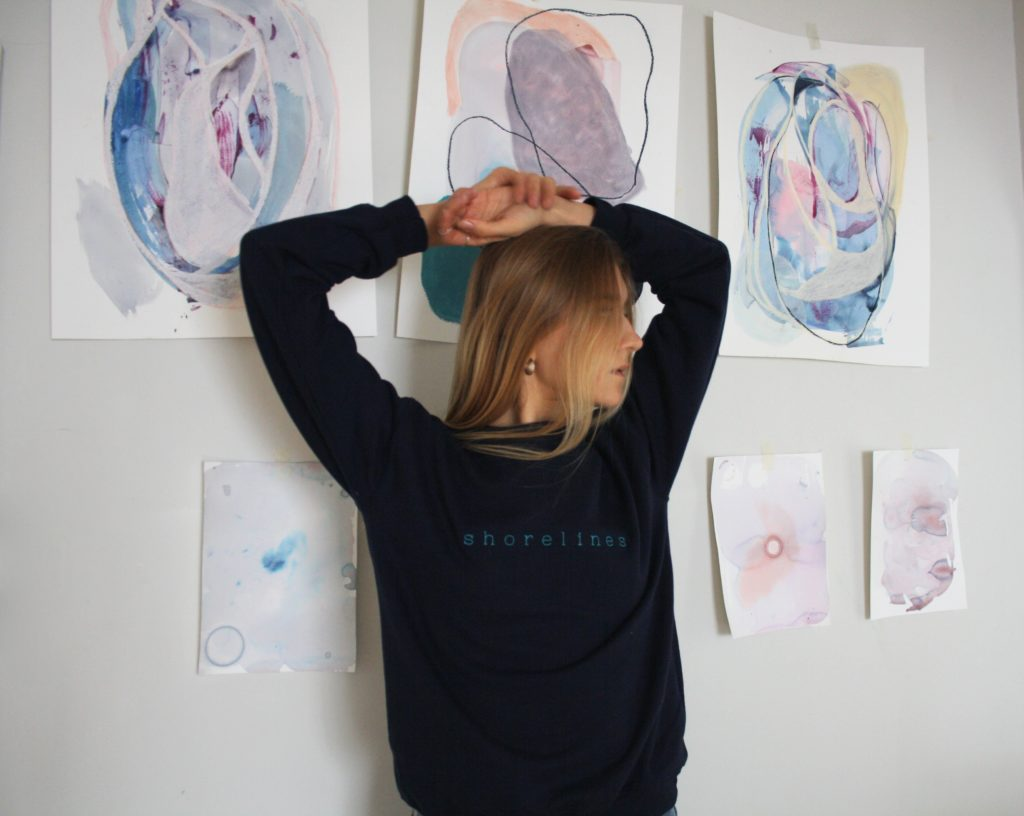 standing in front of some paintings in the blue LYS sweater