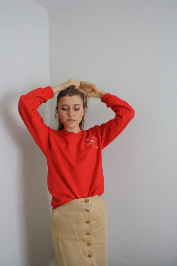 wearing the red LYS sweater with a light peach button up skirt