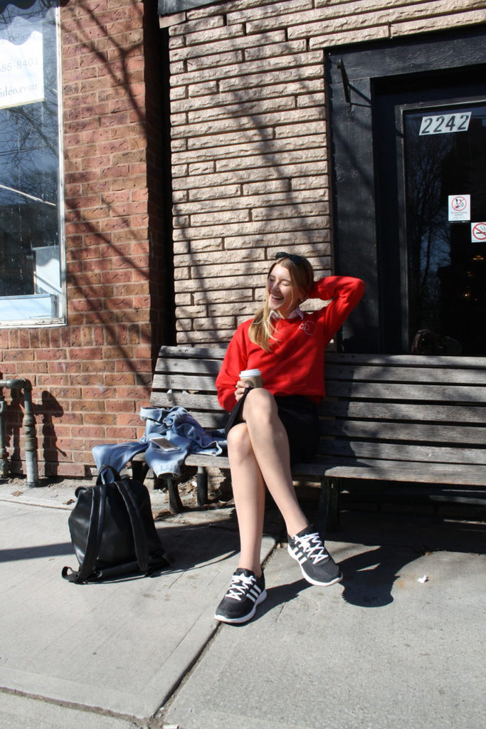 sitting outside a coffee shop on a bench