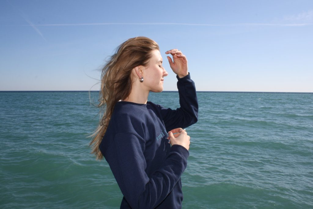 standing on profile on the beach in the blue LYS sweater