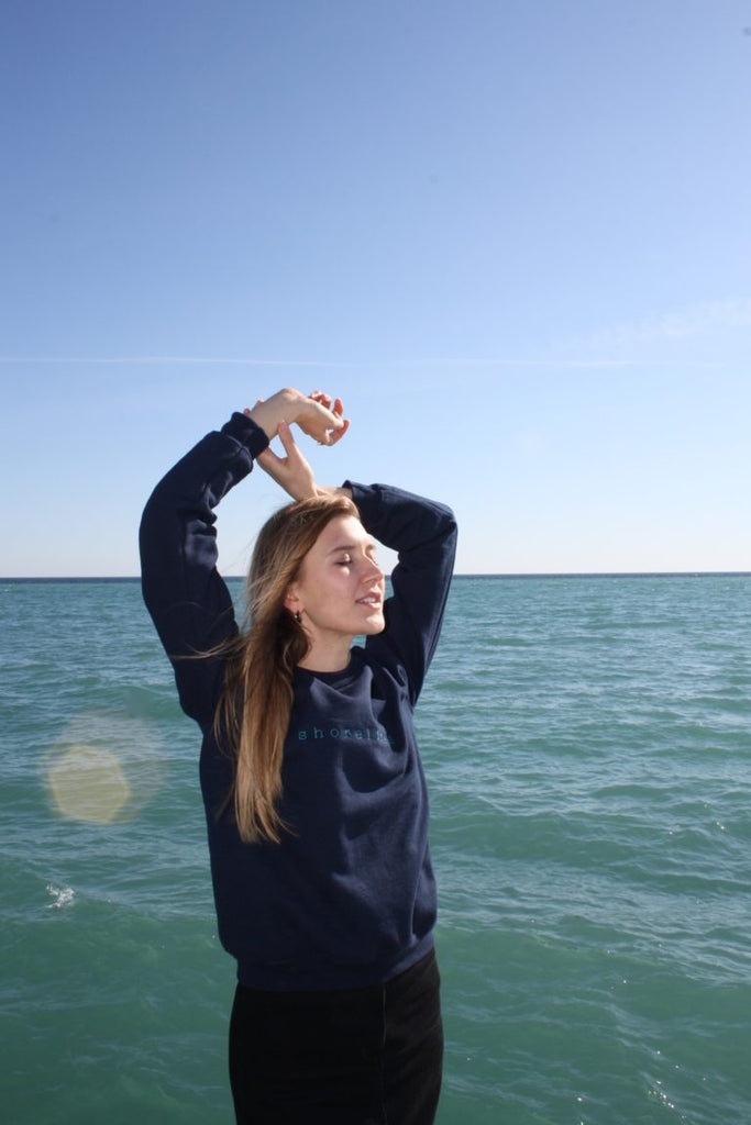 standing on front of the water in the blue LYS sweater