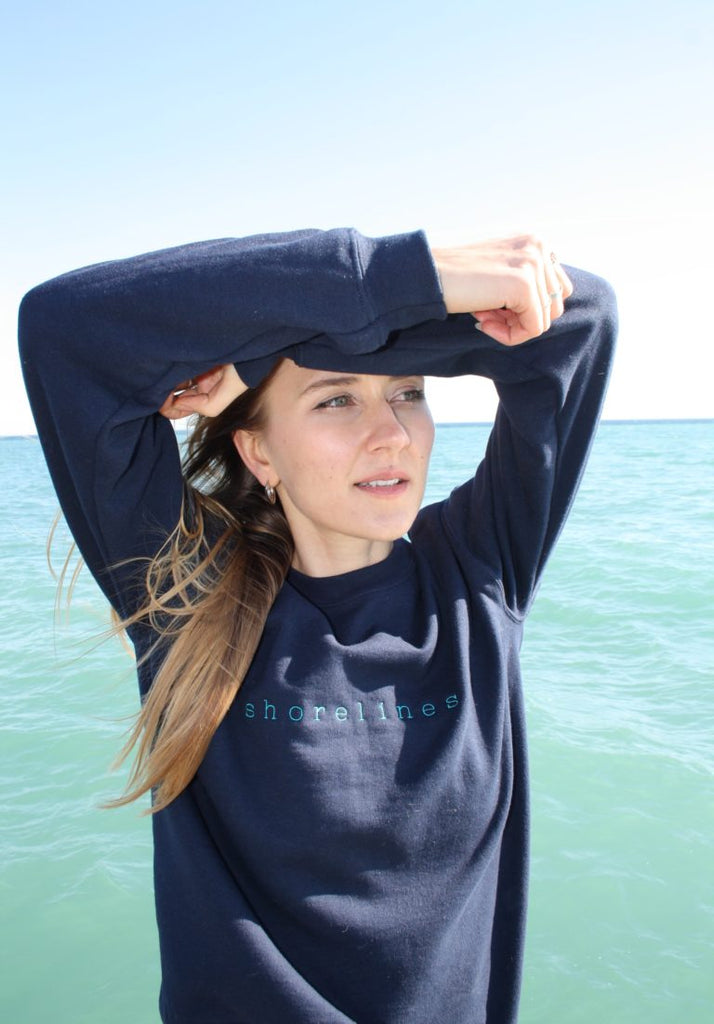 standing in front of the water in the blue LYS sweater