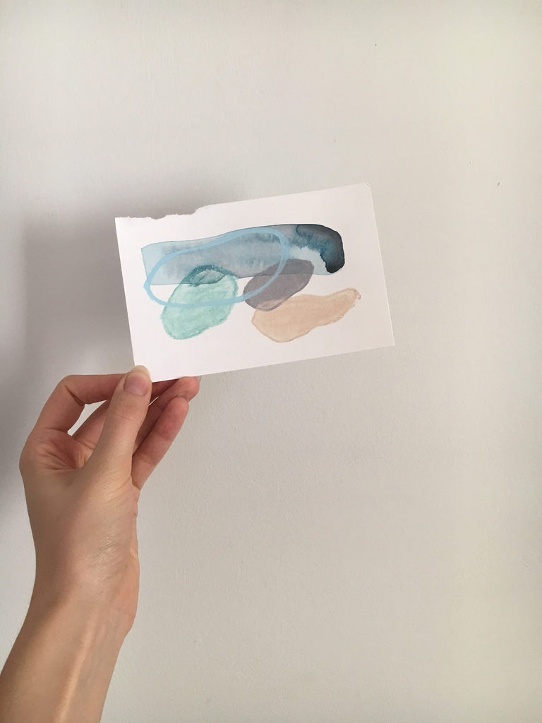 small abstract painting held up against a white wall