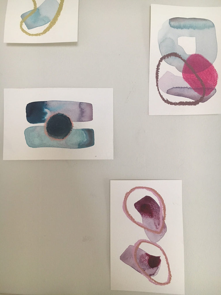 small abstract paintings grouped on a white wall