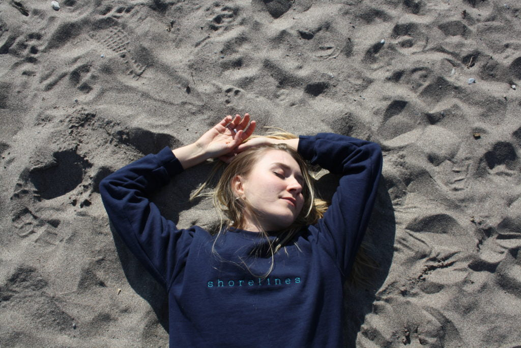 laying in the sand eyes close in the blue LYS sweater