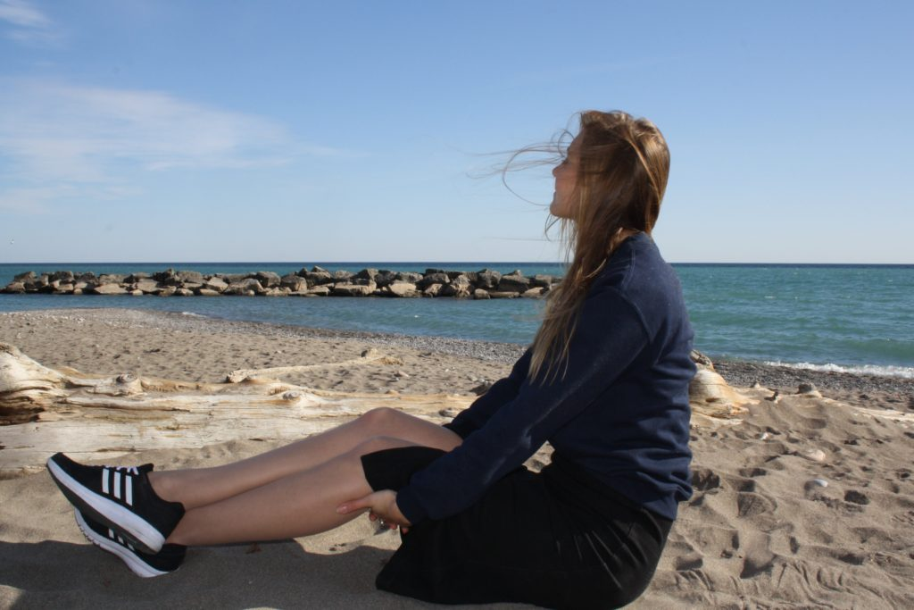 sitting on the beach with legs stretched out