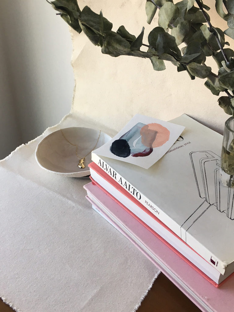 photo set up with some books and a sprig of eucalyptus