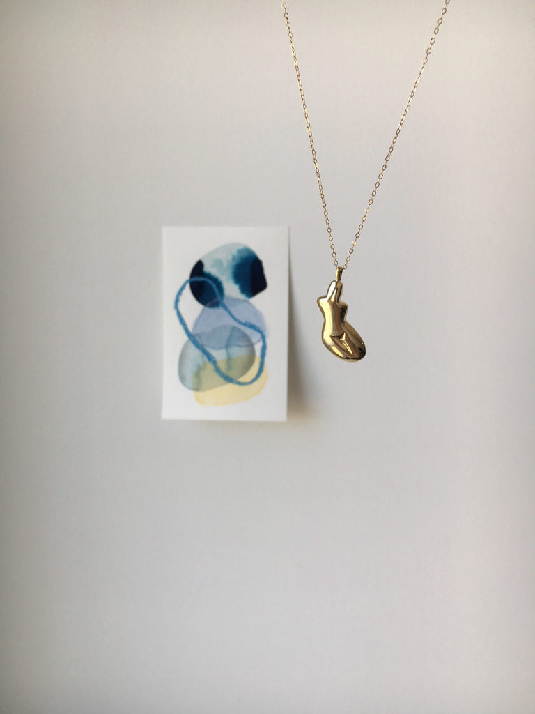 the female forma necklace next to a small abstract painting with blue and yellow