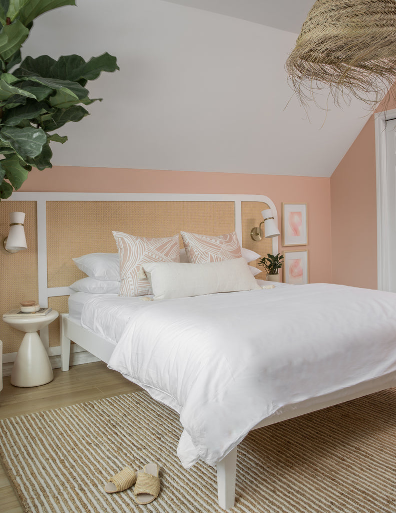 bedroom with pink wall, and white bedding