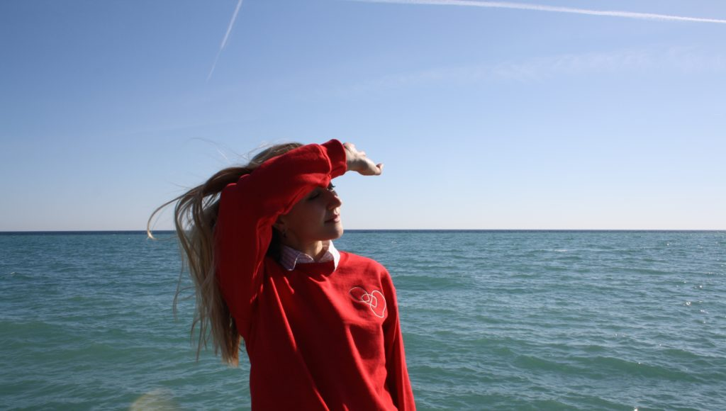shielding my eyes from the sun on front of the water in red LYS sweater