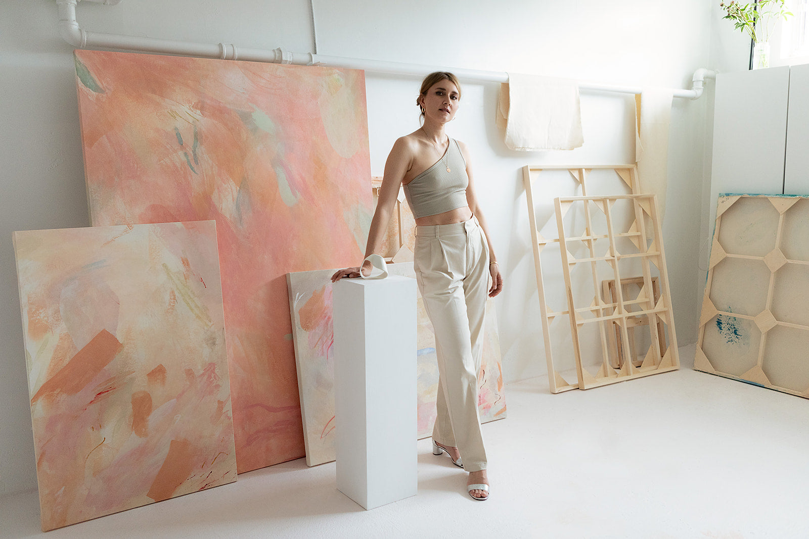 Oksana Berda the artist stands in her light filled studio surrounded by paintings