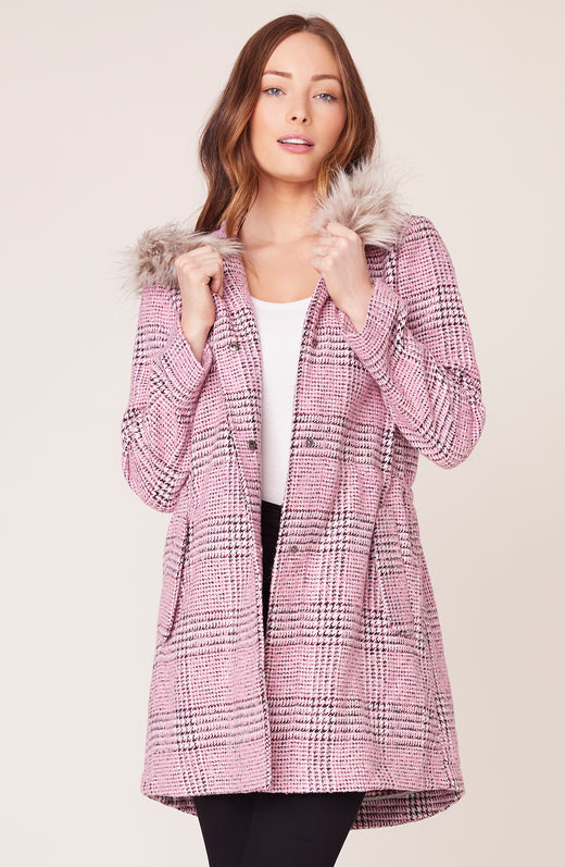 Model wearing pink plaid coat with faux fur hood