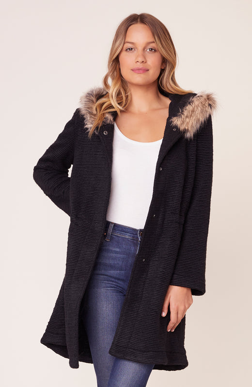 Model wearing black jacket with faux fur hood