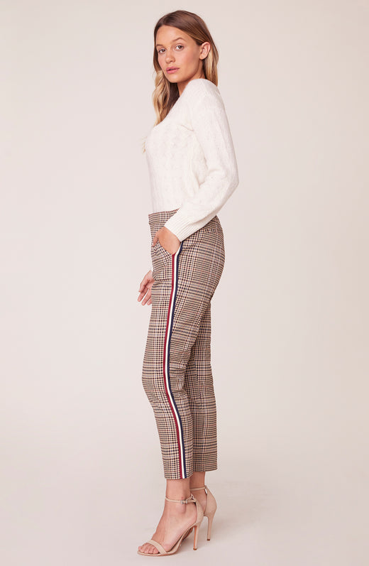 Side view of model wearing plaid trousers with stripe side