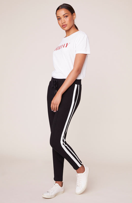 Model wearing athletic jogger pants with white striped side