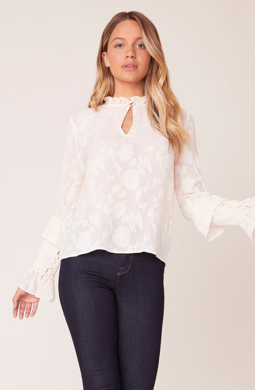 Model wearing ruffled white blouse