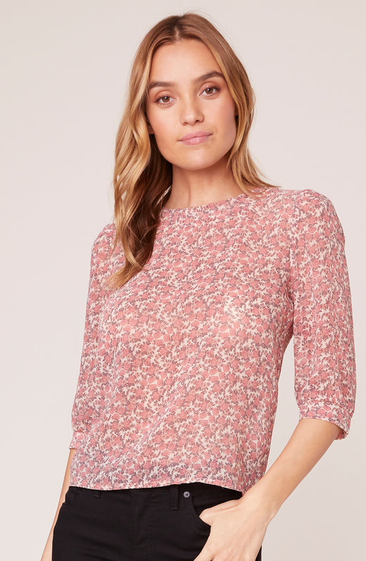 Model wearing a disty daisy print top with 3/4 sleeves