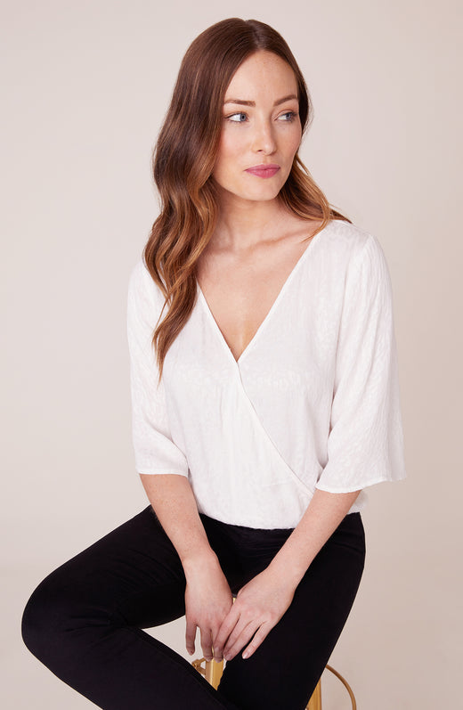 Model wearing white cross front top