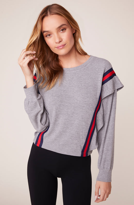 Model wearing super soft sweater with ruffle detail and red stripe