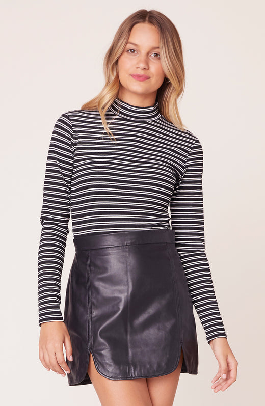 Model wearing long sleeve striped turtle neck top