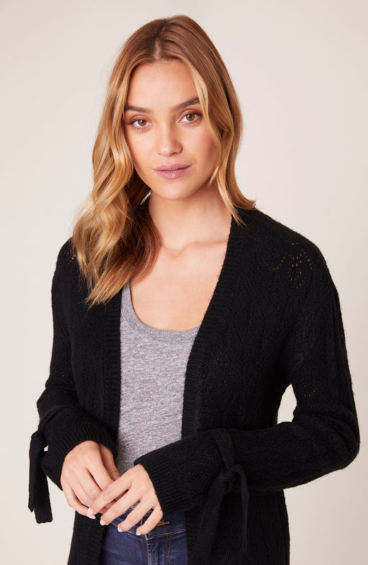 Model wearing super soft cardigan sweater with tie wrists