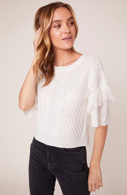 Model wearing short sleeve sweater with fringe detail