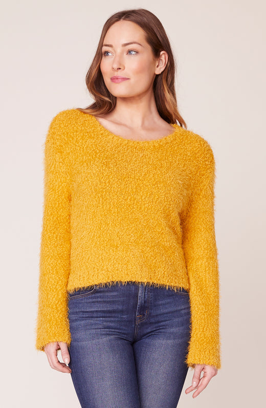 Model wearing fuzzy yellow sweater