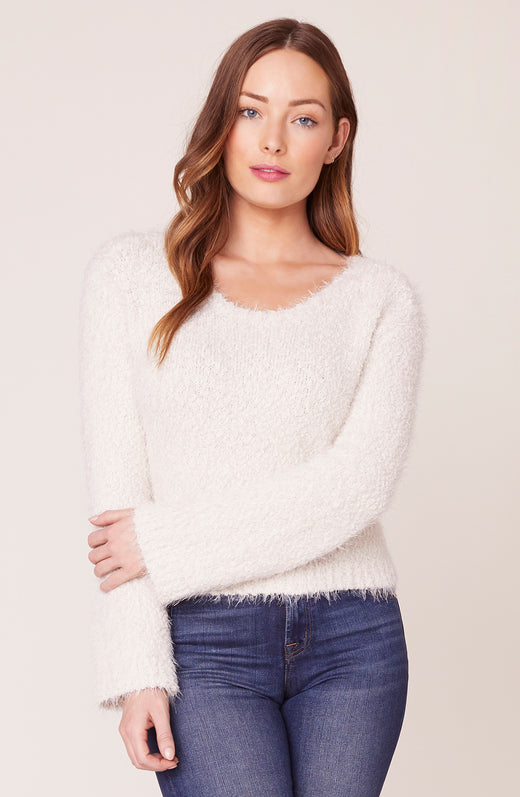 Model wearing fuzzy cream sweater