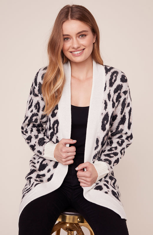 Model sitting in chunky leopard cardigan