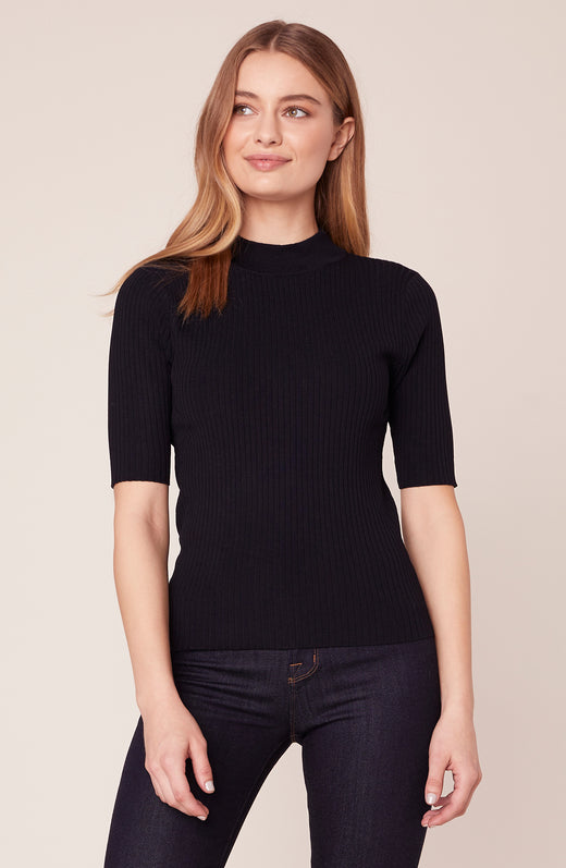 Model wearing black mock turtle neck top