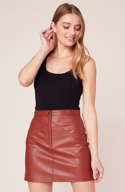 Model wearing rust leather mini skirt