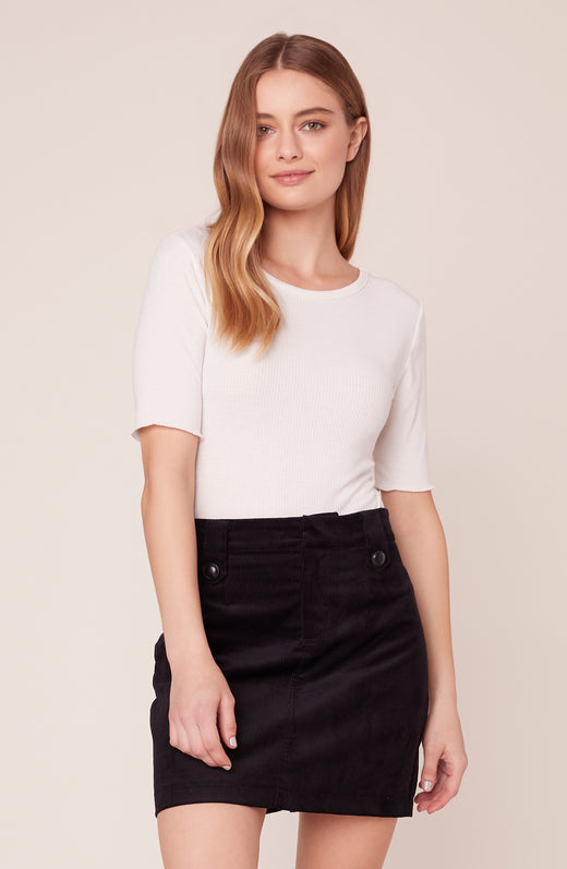 Model wearing black corduroy mini skirt