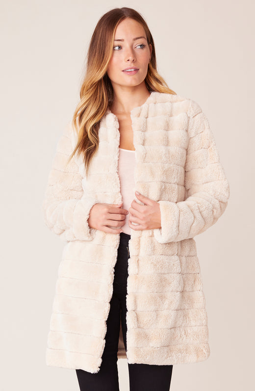 Model wearing ivory faux fur coat
