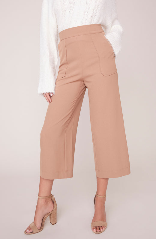 Model wearing camel colored cropped pants
