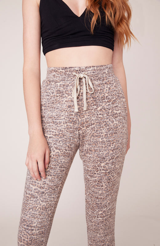 Close up of model wearing leopard printed joggers