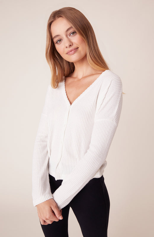 Model wearing white long sleeve top