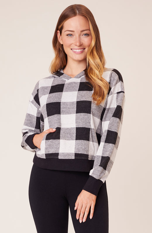 Model wearing grey and black buffalo plaid sweatshirt
