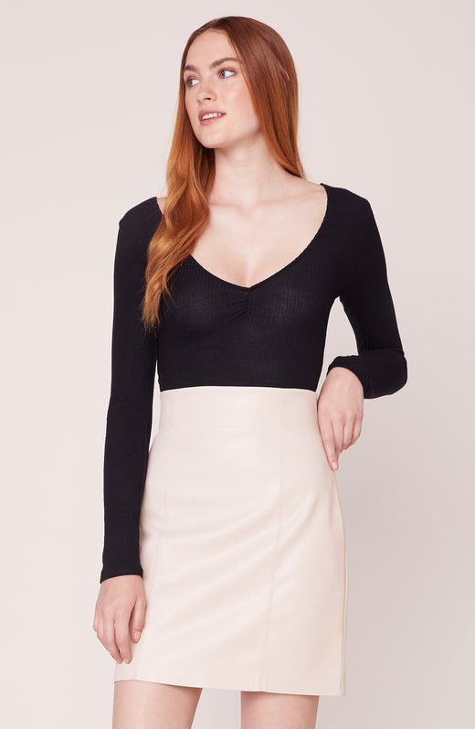 Model wearing black bodysuit with cream skirt