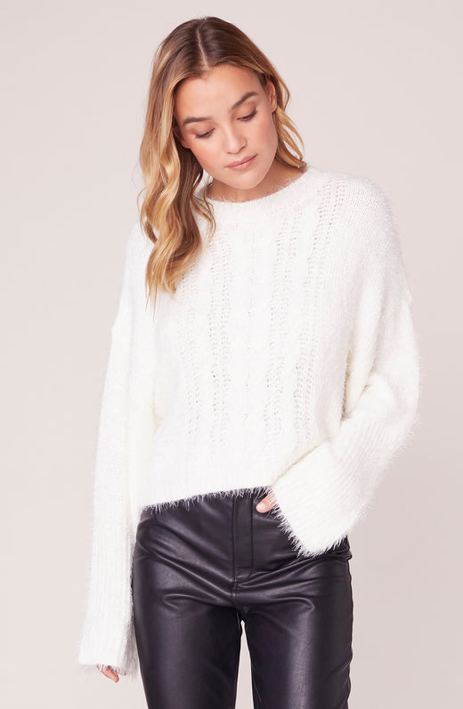 Model wearing fuzzy long sleeve ivory sweater