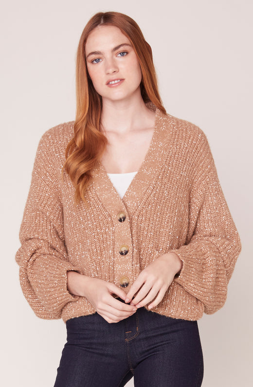 Model wearing cropped camel speckled cardigan sweater