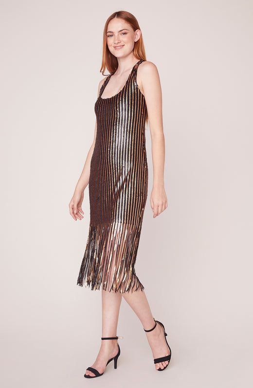 Model wearing gold and black striped dress