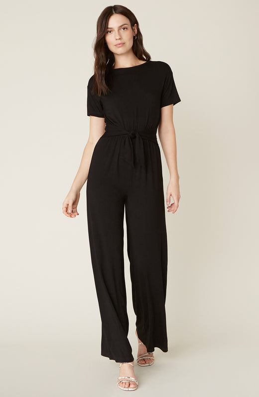 Model wearing black jumpsuit with tie waist