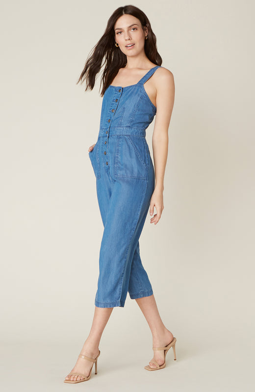 Model wearing cropped denim jumpsuit