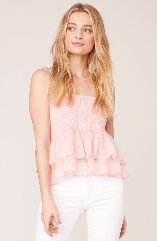 Model wearing sleeveless ruffle blouse