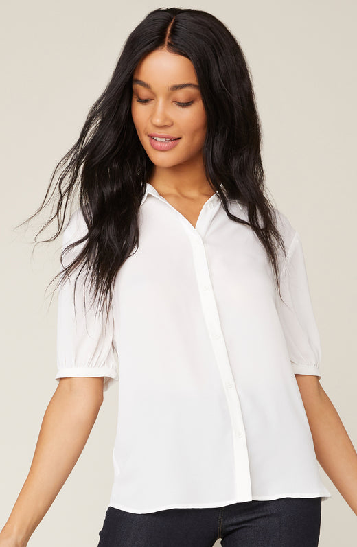 Model wearing button up ivory blouse