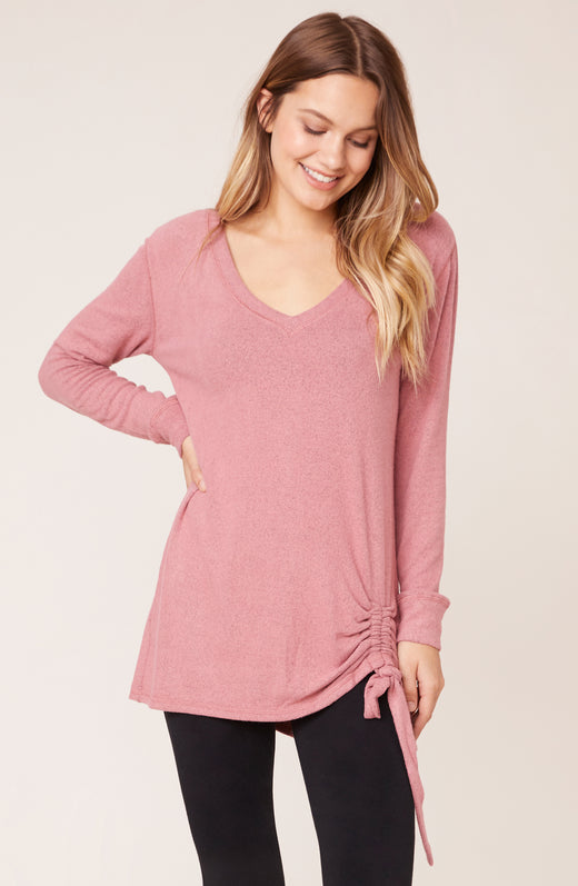 Model wearing pink sweater with cinched tie hemline