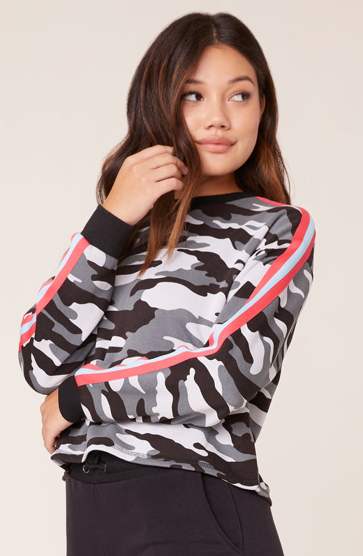 Model wearing camouflage sweater with pink contrast stripe