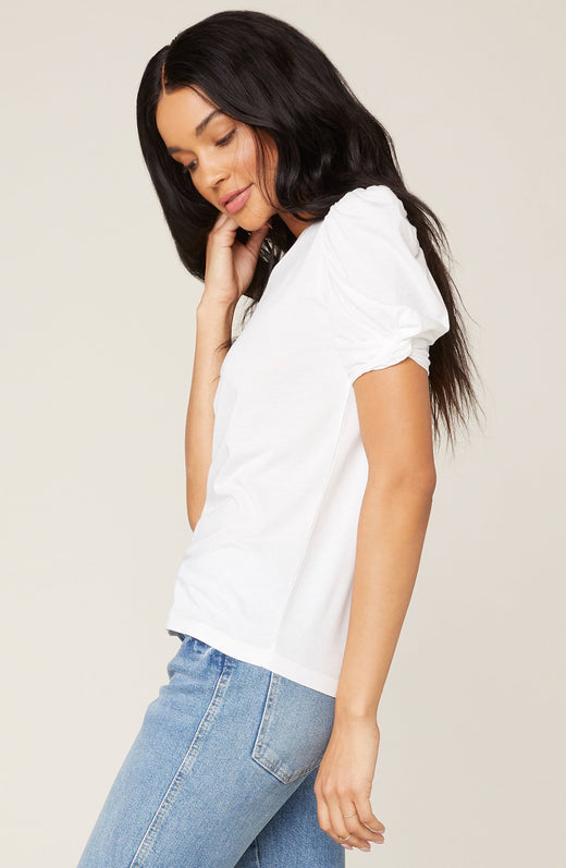 Side view of model wearing white puff sleeve top